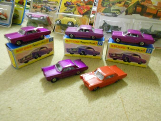 Hier sind Varianten des Pontiac GP Sports-Coupe LS 22-A von Matchbox Superfast abgebildet, darunter eine in dunkel-lila-metallic, mit kleineren 5-Spoke-Wheels, ohne Silber-Trimm und eine Brasilien-Variante.